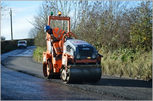A man in high vis riding a road roller on a fresh stretch of road