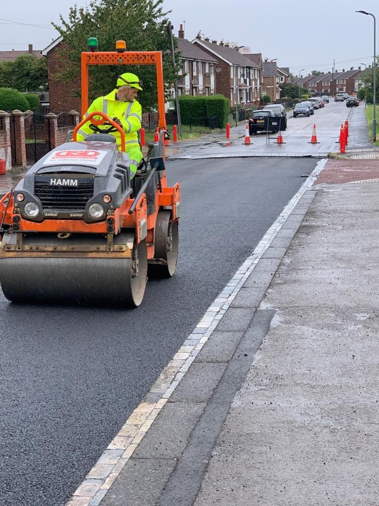 man in high vis driving a road roller on a fresh road surface