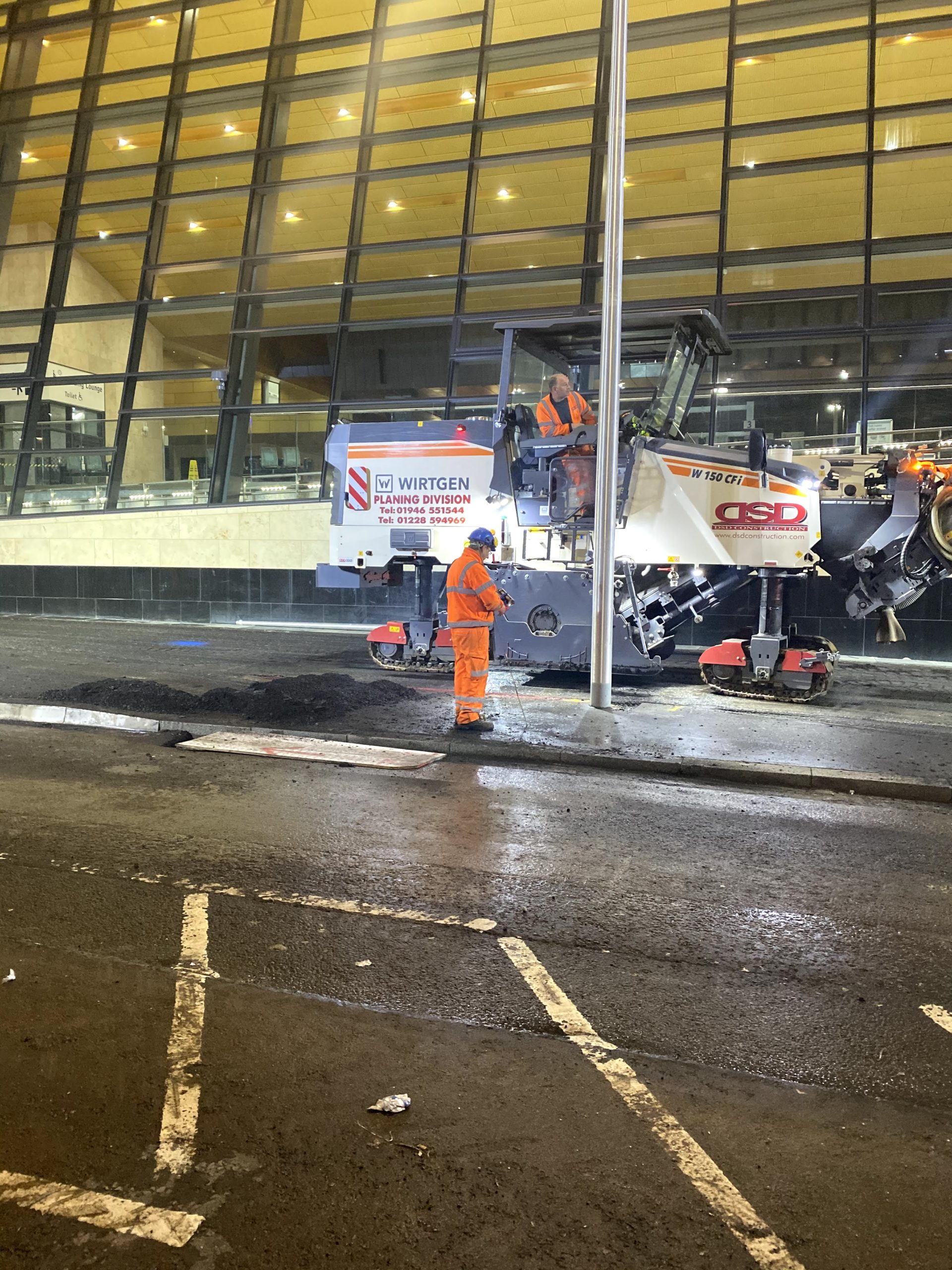 Men in orange high vis working at a train station at night