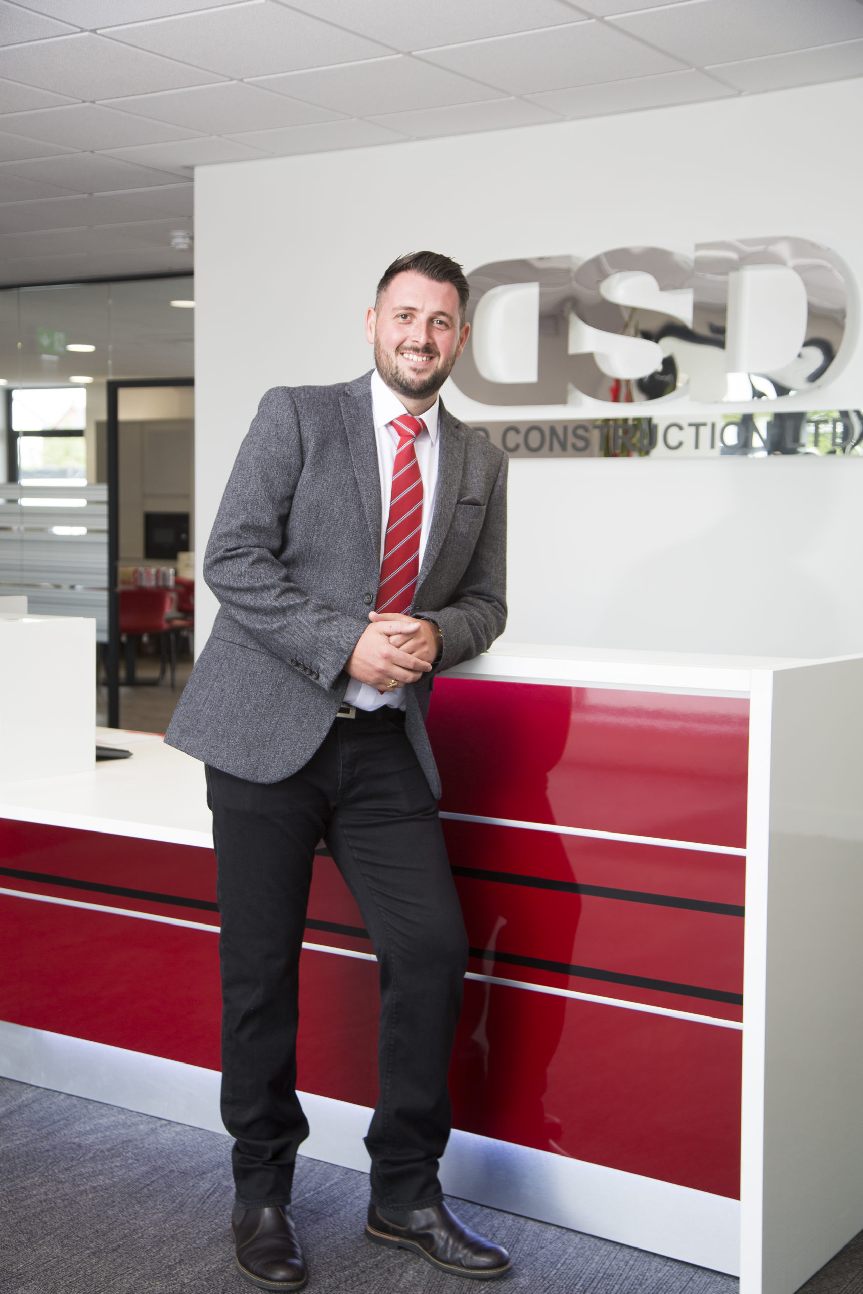General manager in a suit leaning on reception desk