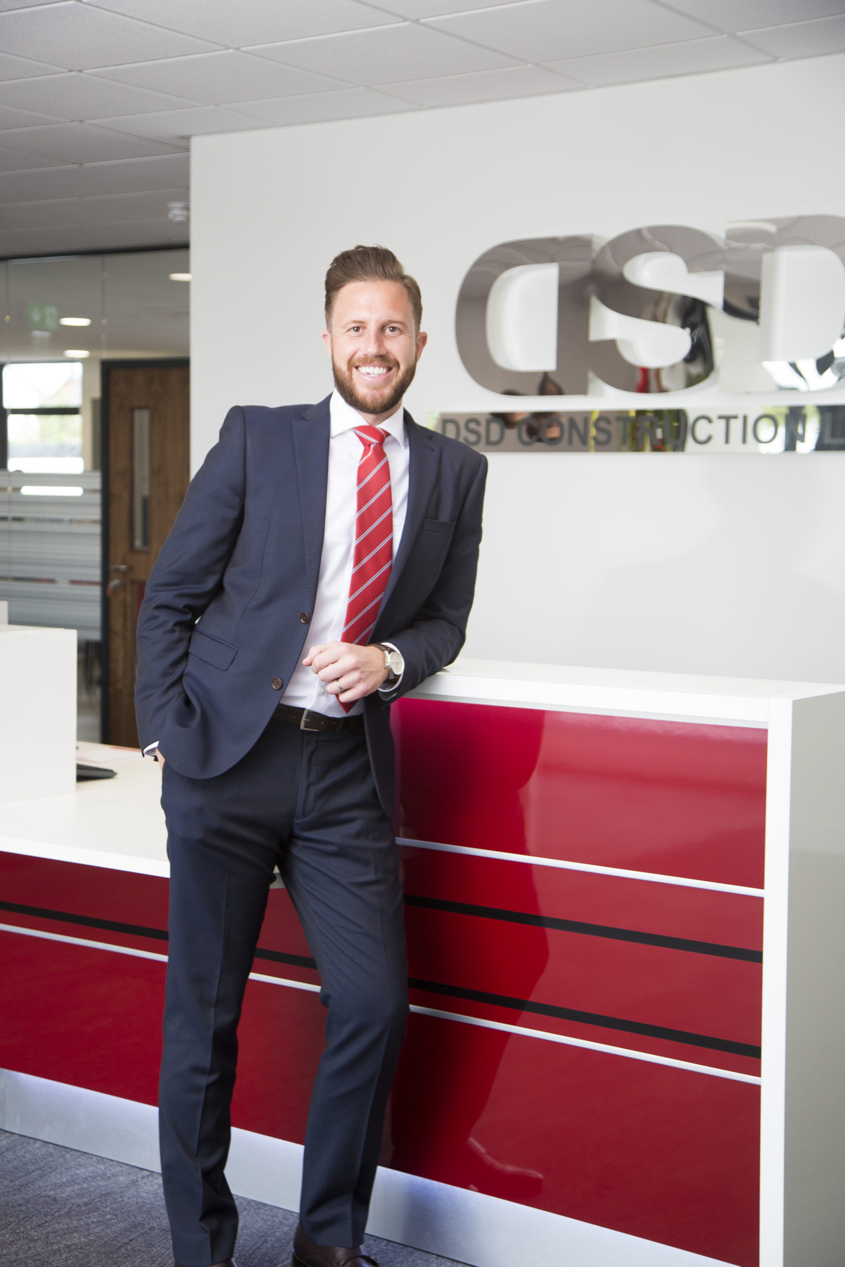 Commercial manger in a suit leaning on reception desk