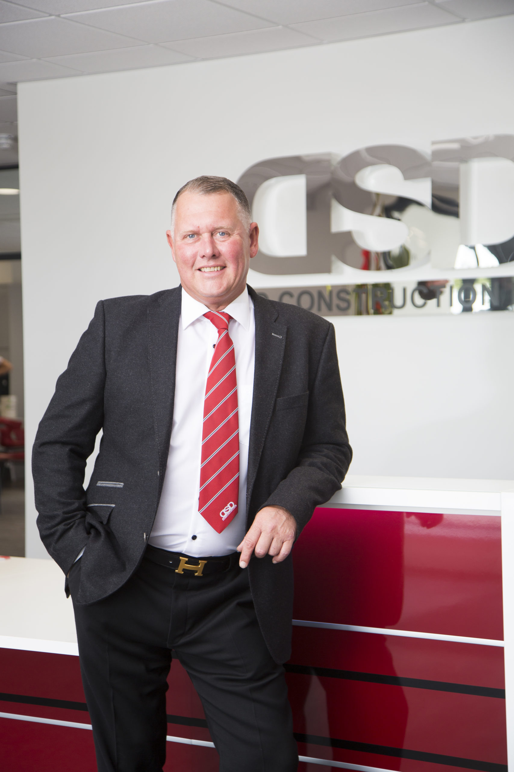 Managing director in a suit leaning in reception desk