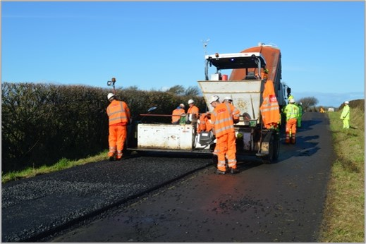 Multiple men in high vis laying a fresh road surface